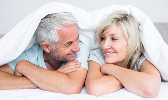 ベッドに横たわって笑顔で見合っている中年期の夫婦|副腎疲労blog