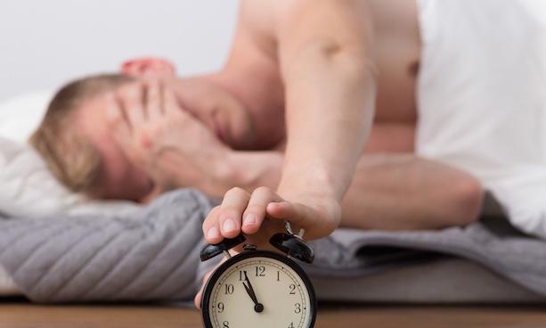 目覚まし時計をおさえて辛い様子の男性|副腎疲労blog