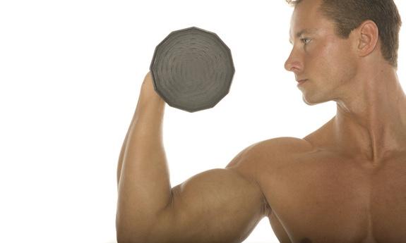 ボディービルダーがダンベルで腕の筋肉を鍛えているところ|副腎疲労blog