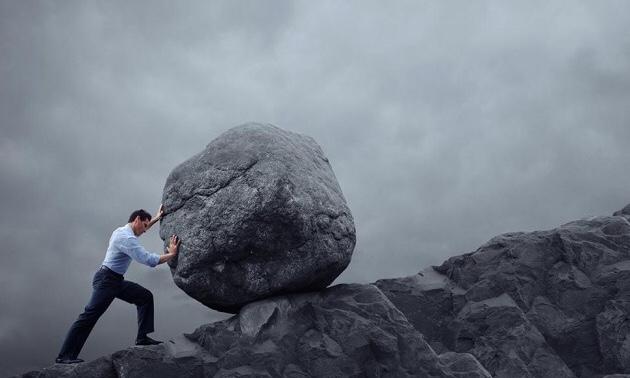 大きな石を転がして坂を登ろうとしているスーツ姿の男性|副腎疲労blog