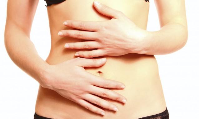 お腹を両手で触っている女性|副腎疲労blog