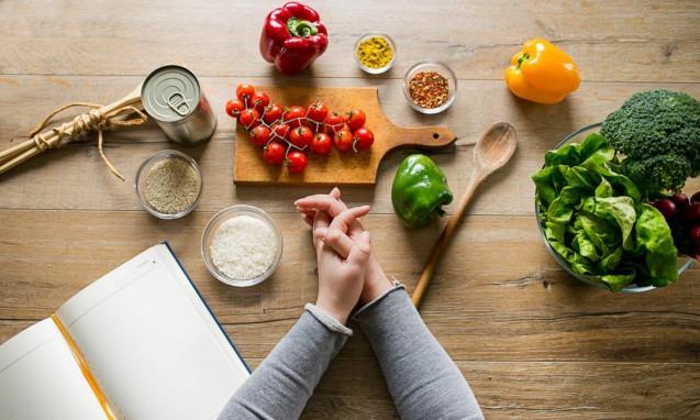 机の上に置かれた綺麗な野菜と女性の手の組んだ写真|副腎疲労blog